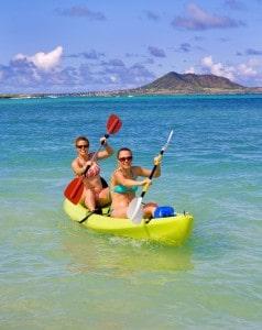 Two sisters paddling a kayak in Hawaii